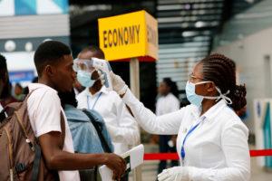 A health worker checks the temperature of a traveller in coronavirus screening at Kotoka International Airport, Accra, Ghana. (Francis Kokoroko/REUTERS)